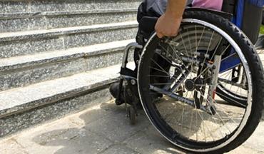 una sedia a rotelle davanti a una scalinata